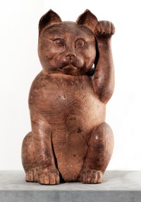 A wooden sculpture of a seated cat with one front paw raised in the air
