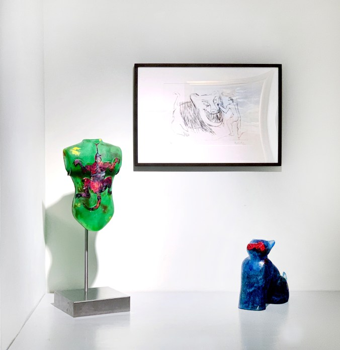 Installation shot of two glass sculptures underneath a print