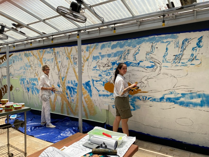 Isabel De Obaldia and her assistant painting the mural in the courtyard