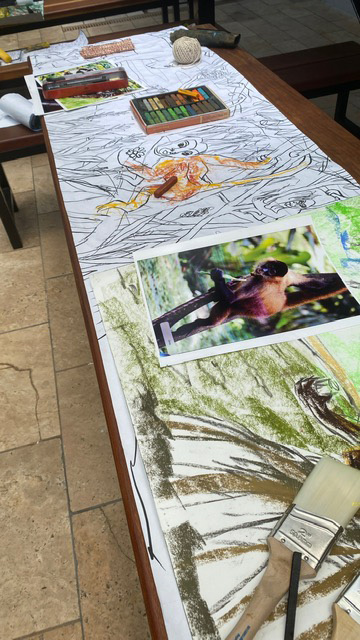 Photograph of sketches and a photo of a monkey, used for preparation to paint a mural