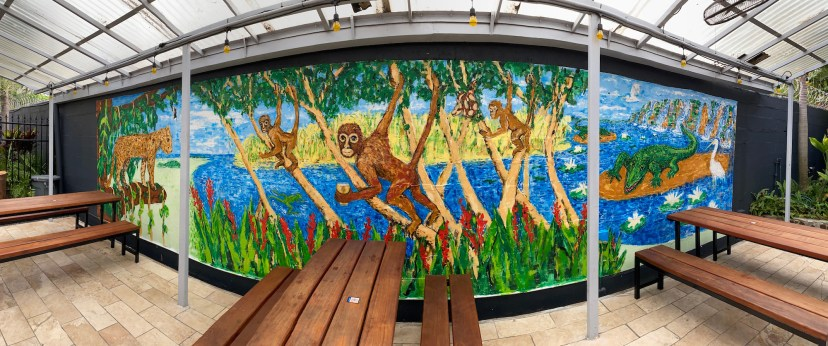 Photo of a vibrant mural in a courtyard featuring monkeys, a jaguar, and a crocodile