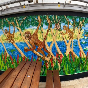 A vibrant painted mural featuring monkeys, a jaguar, and a crocodile, set in the courtyard of a brewery.