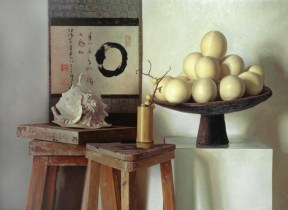A painted still life of two wooden stools, a conch shell, and a wooden tray filled with eggs resting on a white pedestal. A Japanese painting with calligraphy hands on the wall behind the arrangement.
