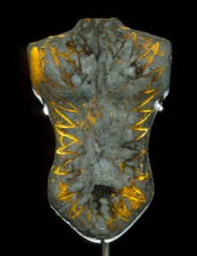 Grey glass sculpture of a torso engraved with a golden starburst