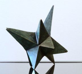 A ten pointed bronze star with a dark green patina. The points of the star are varying lengths.
