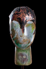 Green and grey glass sculpture of a head with a metal helmet