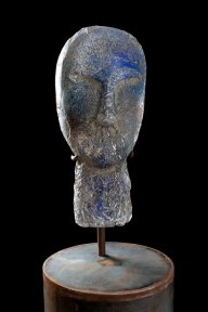 Glass sculpture of a primitive head in blue and grey tones