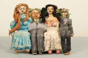 A Papier-mâché sculpture showing four seated figures with their eyes closed. The two men wear old fashioned gray suits and have leaves on their heads. One woman has a bright blue dress with red yarn hair, and the other has a white dress with pink dots and black yarn hair.