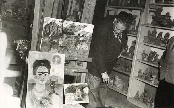 A black and white photograph of a man looking at an easel with three paintings on it