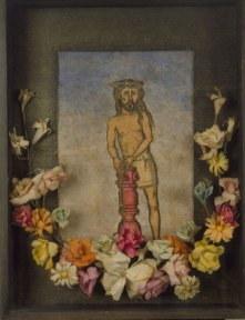 A drawing of Christ tied with rope to a waist high red column. The drawing is framed in a black shadowbox with an arch of multicolored flowers along the bottom.