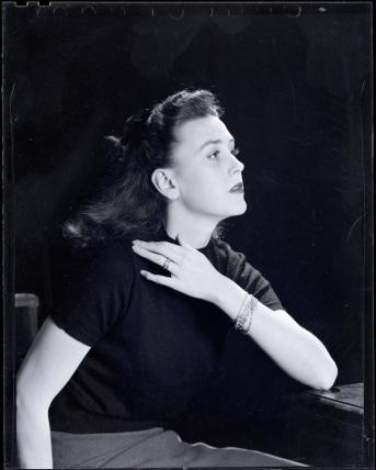 Black and white photograph of a glamorous young woman in a black sweater posing in profile