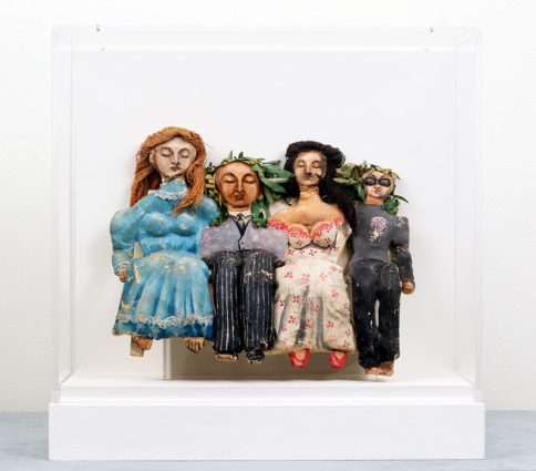 A papier-mâché sculpture of four seated figures with their eyes closed, displayed in a vitrine