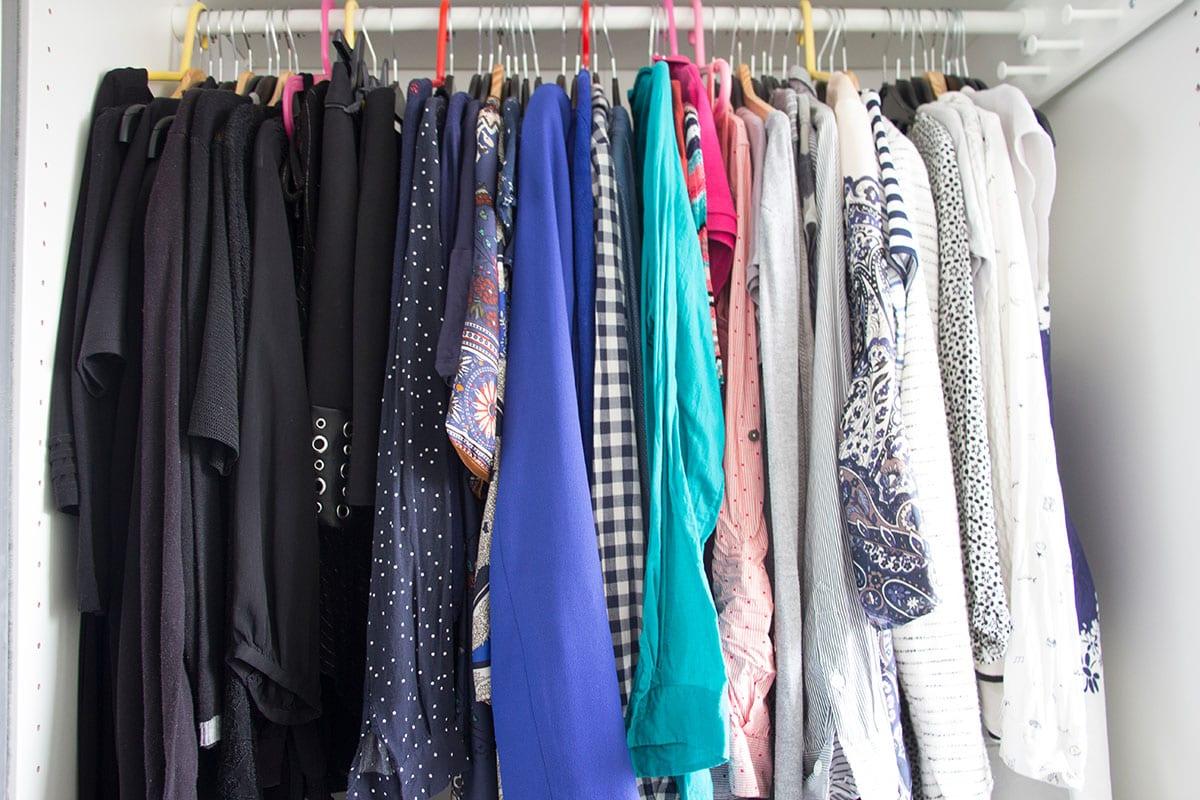 Kleiderschrank ausmisten – die Kleidungsstücke sind nach Farben eingeräumt
