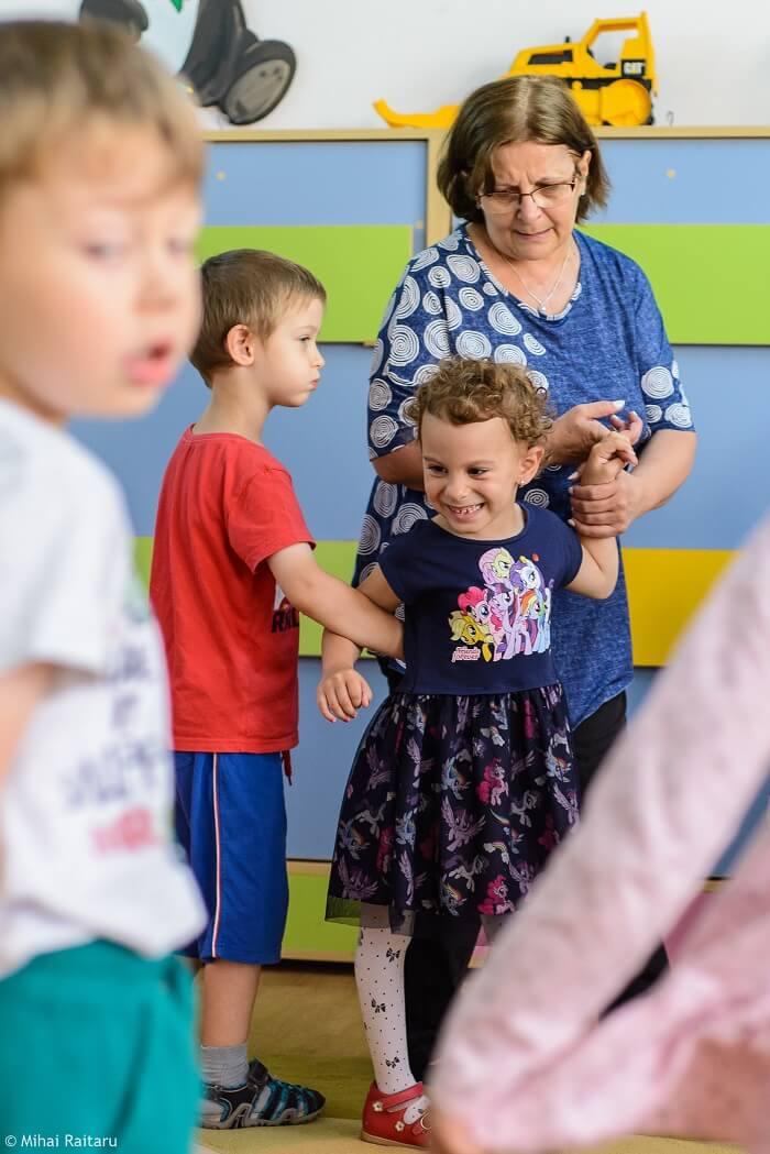 Cu doamna educatoare Elena Duță și colegii Denisei, ajutată să danseze.