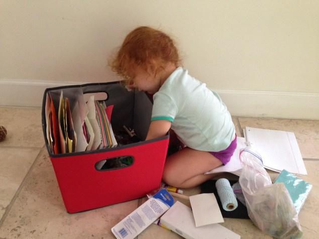 Cristina no resiste la curiosidad de ver qué tesoros halla en la caja de pinturas.