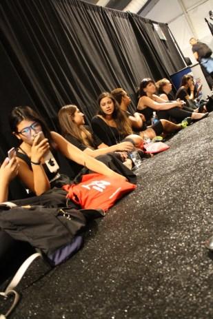 Las chicas que ayudan a vestirse a las modelos esperaron pacientemente.