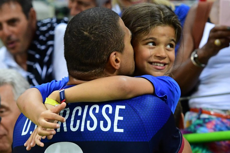 France's centre back Daniel Narcisse kisses his daughter Aimy after the men's preliminary round Group A handball match between Qatar and France during the Rio 2016 Olympic Games at the Future Arena in Rio de Janeiro on August 9, 2016. / AFP / FRANCK FIFE        (Photo credit should read FRANCK FIFE/AFP/Getty Images)