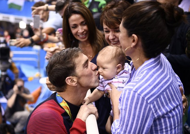 TOPSHOT - USA's Michael Phelps (L) kisses his son Boomer next to his partner Nicole Johnson (R) and mother Deborah (C) after he won the Men's 200m Butterfly Final during the swimming event at the Rio 2016 Olympic Games at the Olympic Aquatics Stadium in Rio de Janeiro on August 9, 2016.   / AFP / Martin BUREAU        (Photo credit should read MARTIN BUREAU/AFP/Getty Images)