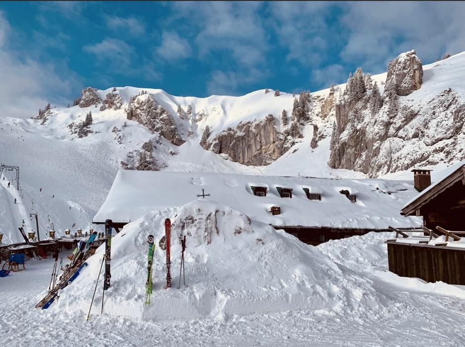 Ein Hüttenwochenende in den Bergen. Eine eingeschneite Holzhütte, mit in den Schnee gesteckten Skiern. Ein blauer Himmel mit leichten Schleierwolken im Hintergrund
