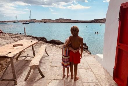 Zwei Geschwister am Meer, arm in Arm schauen sie auf das Wasser. Es sind Ferien