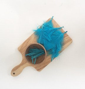 Exploring blue for sensory bottles using feathers and craft sticks.