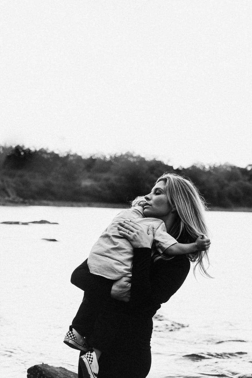 serene woman hugging son on river coast
