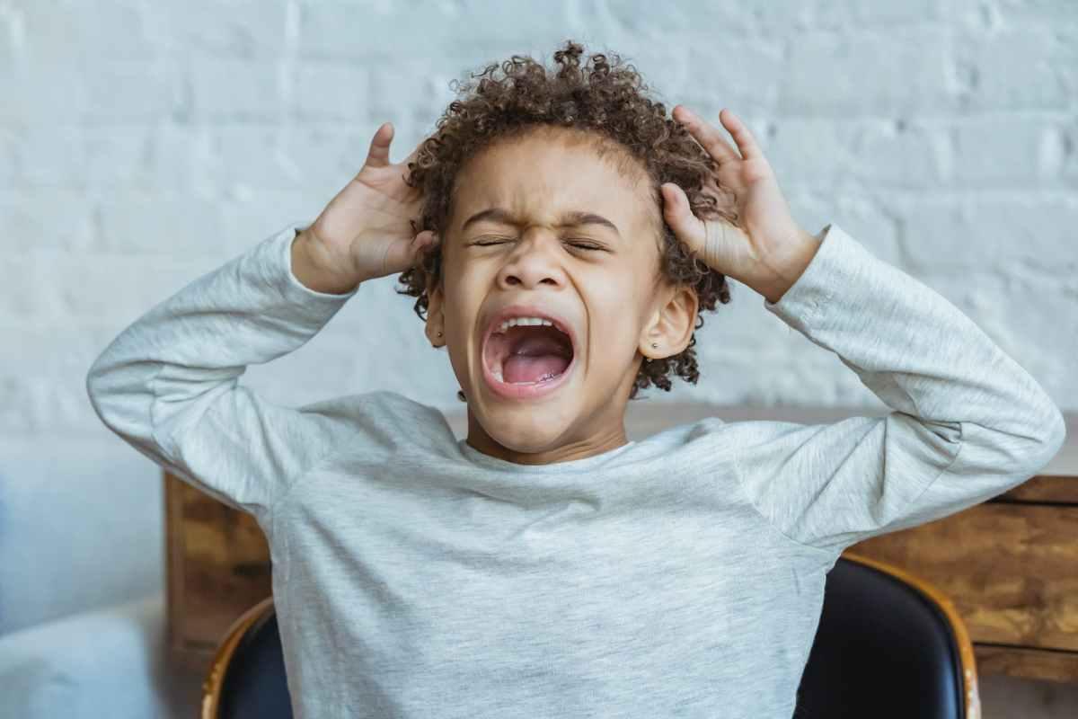 desperate black boy shouting in room