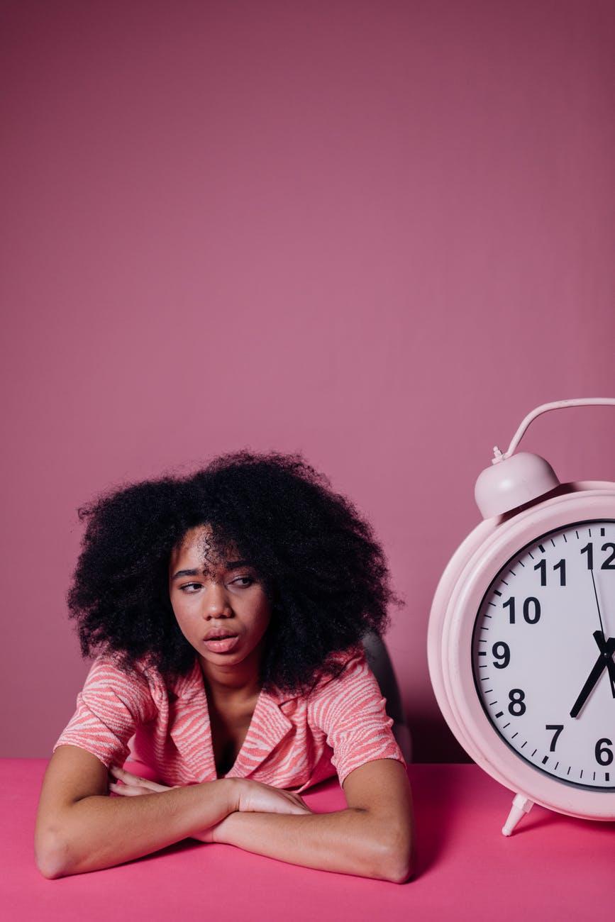 woman looking bored beside a big alarm clock