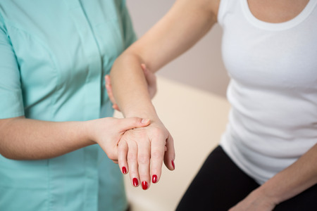 42425056 - close-up of pysiotherapist holding woman's forearm