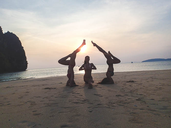 three girls doing yoga in the sunset