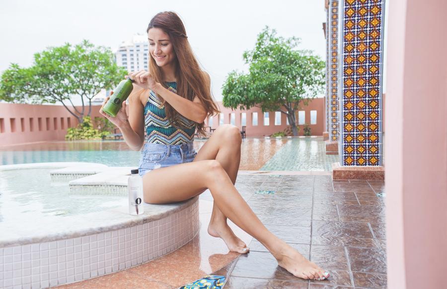 girl opening green juice bottle thailand