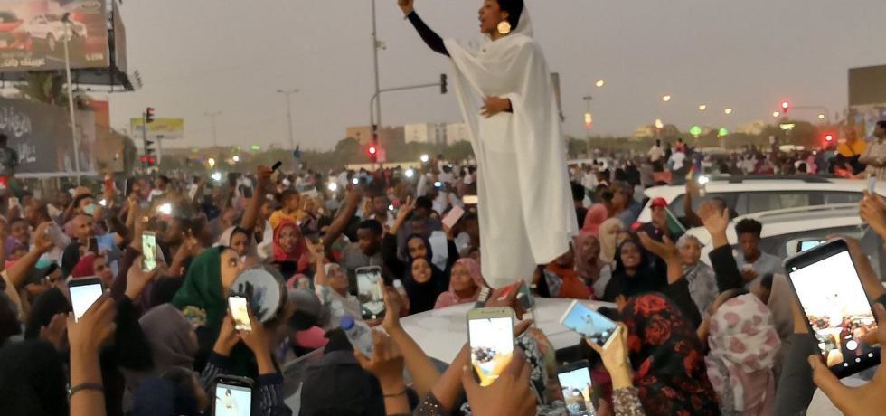 Alaa Salah giving a speech in front of crowd on top of a car.