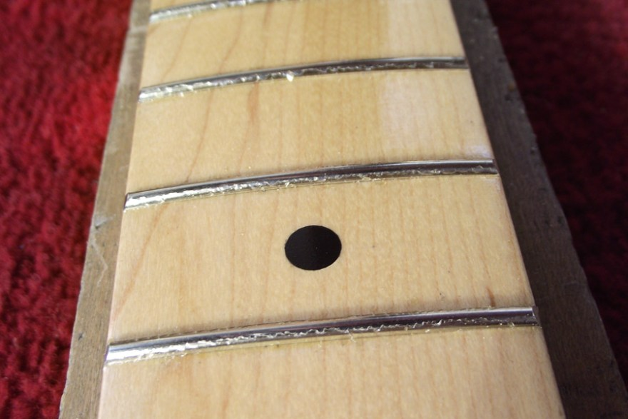 Showing the frets scraped clear of lacquer