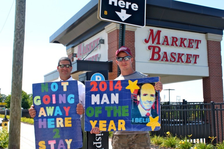 John Meletis, left, and Spencer Worth, hold signs outside the Manchester, NH, Market Basket.