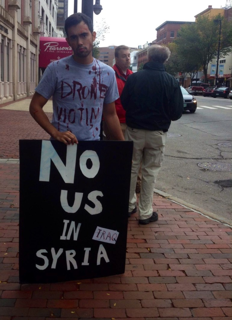 Carlos Morales holds a sign along Elm Street in Manchester, protesting U.S. involvement in Syria and Iraq.