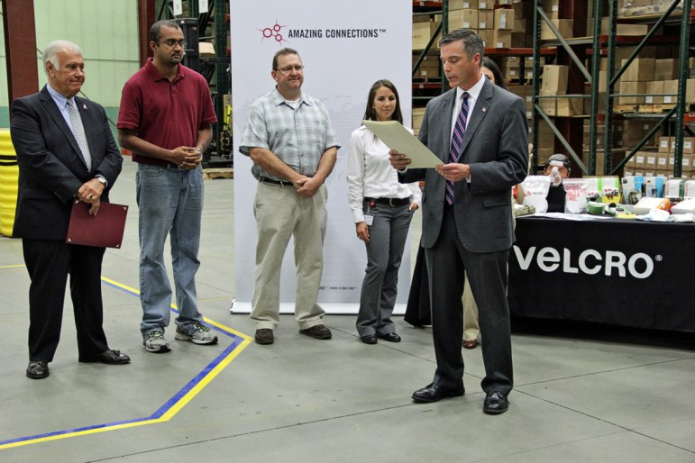 """MANCHESTER, NH – New Hampshire joined the rest of the nation in celebrating Manufacturing Day on Friday, concluding a week of events highlighting the importance and opportunities in state's top industry with a ceremony at Velcro USA. """"Thank you for joining us today to recognize New Hampshire's rich manufacturing heritage and celebrate its vibrant future,"""" Velcro USA New Hampshire Operations Manager Donald Boulanger told the gathering, which included Manchester Mayor Ted Gatsas and state Sens. Lou D'Allesandro and Donna Soucy. While all 50 states recognize Manufacturing Day, New Hampshire is the only one that's declared Manufacturing Week. In its second year, New Hampshire Manufacturing Week organizers connected 41 companies across the state with over 1,000 high school students and their teachers touring their plants to see what happens in this industry that is an important driver of the state's economy. In addition, about 500 people took part in tours and open houses hosted by the state's community colleges and career-technical education centers. """"Velcro USA is honored to host today's recognition ceremony,"""" Boulanger said. """"We have been a part of New Hampshire's manufacturing community for nearly 60 years and are committed to its growth and evolution. This week, we hosted groups of students for tours of our facility here. We're helping to inspire and encourage the next generation of manufacturing leaders by showing them that today's manufacturing operations are driven by technology and innovation, provide strong career opportunities and, most importantly, help to grow the New Hampshire economy."""" Department of Resources and Economic Development Commissioner Jeffrey Rose read a proclamation issued by Gov. Maggie Hassan, declaring Manufacturing Week. He noted that manufacturing in the state employs over 66,000 people. """"It's important that we have an event like this every year because it elevates the profile of the state's largest industries,"""" Rose said. Gatsas also pre"""