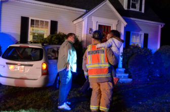 A firefighter holds a child who was uninjured after a van she was in hit a house on Rockland Street.