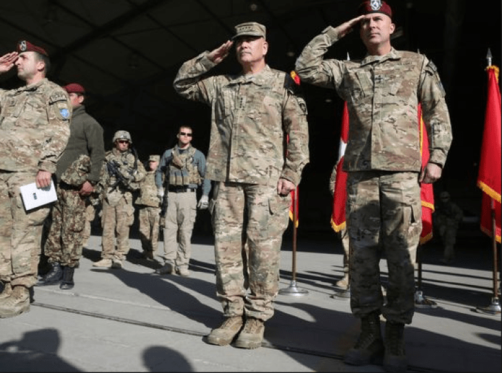 International Security Assistance Force Joint Command, Lt. Gen. Joseph Anderson, right, and commander of International Security Assistance Force, Gen. John F. Campbell, center, salute during a flag-lowering ceremony Monday in Kabul. The U.S. and NATO ceremonially ended their combat mission in Afghanistan.
