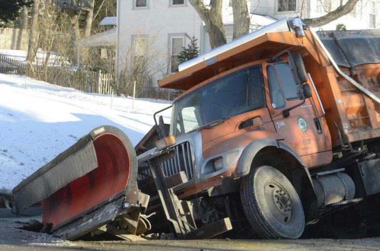 City sander truck stuck in a sinkhole on Kennard Street following water main break.