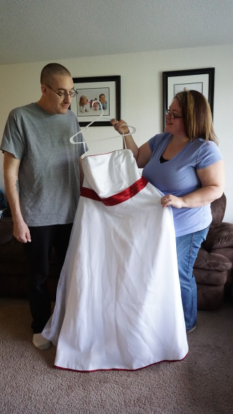 Melissa Fox takes a last look at her wedding dress before she and her kids paint it with a Superman theme as a tribute to her husband Steve, battling cancer.