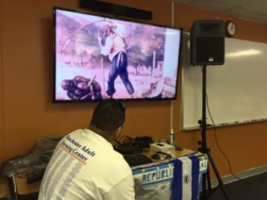 Students watch a video presentation about the history of Puerto Rico.