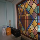 A repurposed stained glass window from St. Peter's chapel adds to the spiritual vibe at Kriss Cosmetics.