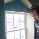 Kriss Blevens looking out a second-floor window of her new salon, with a view of her old stomping ground.
