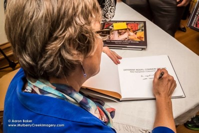 Author Becky Field signs books during the Sept. 17 launch of Different Roots, Common Dreams, in Concord.