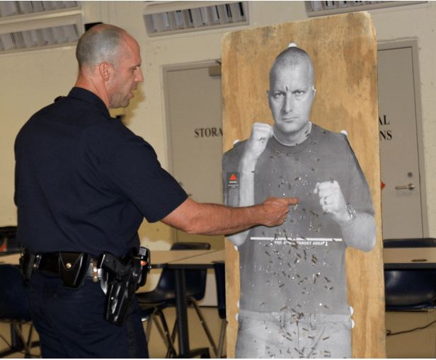 """Officer Paul Rondeau talks to Citizens Academy members about target practice using a cardboard """"target man"""" cutout."""