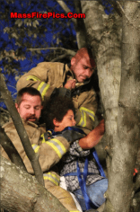 Firefighters work to rescue a boy who became wedged into a tree.