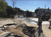 Workers at the site of the road collapse due to a water main break.