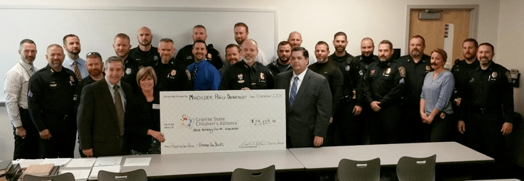 Chief Willard (Center), who is presenting a check to Joy Barrett (holding the check) of Granite State Children's Alliance, surrounded by a handful of the 125 officers who participated in the Beards for Bucks fundraiser, as well as several GSCA board members. Detective Lieutenant Ledoux is pictured in the faux mustache.