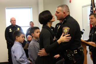 Sgt. Brian Caldwell gets a kiss from wife, Tracy, while his two sons, Ethan and Danny, look on.
