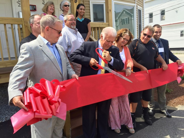 Mayor Ted Gatsas cuts the ceremonial ribbon on a refurbished apartment, the new home for four families, thanks to Families in Transition - New Horizons.
